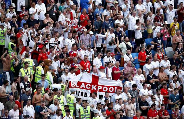 England supporters cheer and hold up flags as they watch Southgate's side demolish Panama in their World Cup fixture