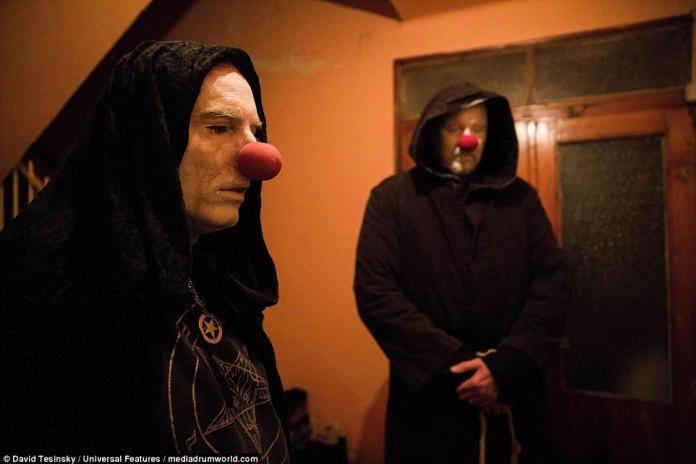 Imagens inquietantes mostrando seguidores de Satanás usando narizes de palhaço e longas túnicas escuras