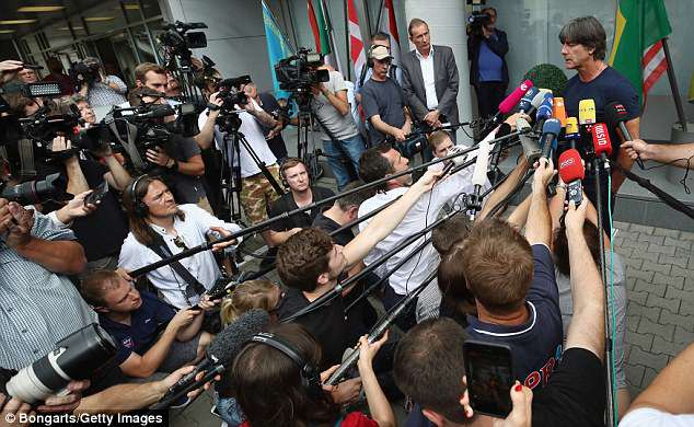 Joachim Lowe faces an army of reporters after landing at Frankfurt International Airport