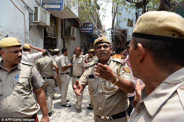 Indian policemen secure the area near a building where 11 family members were found dead inside their home in the neighbourhood of Burari in New Delhi