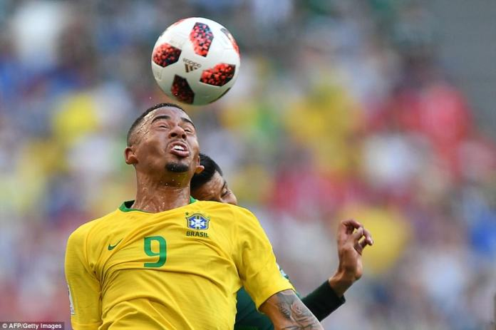 Gabriel Jesus leaps high to plant a head on the ball in front of Hugo Ayala in sweltering conditions in Samara