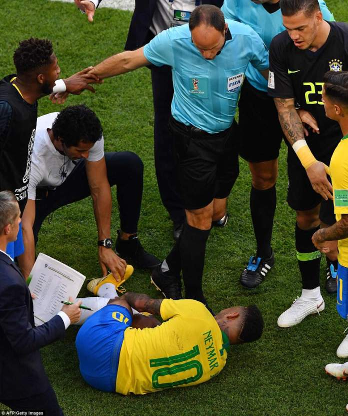 On the sidelines by the dugout a number of players and officials surrounded Neymar who clutched his leg