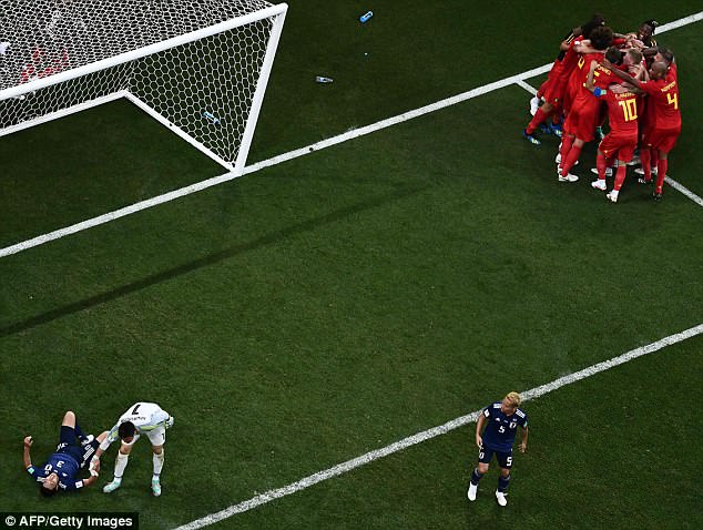 As Belgium celebrate a stunning winner, Japan's players lay strewn on the turf