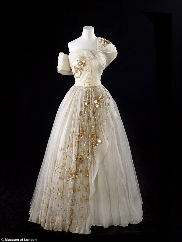 The one-shouldered cream gown features a dramatic tulle skirt and gold embellishment running down it