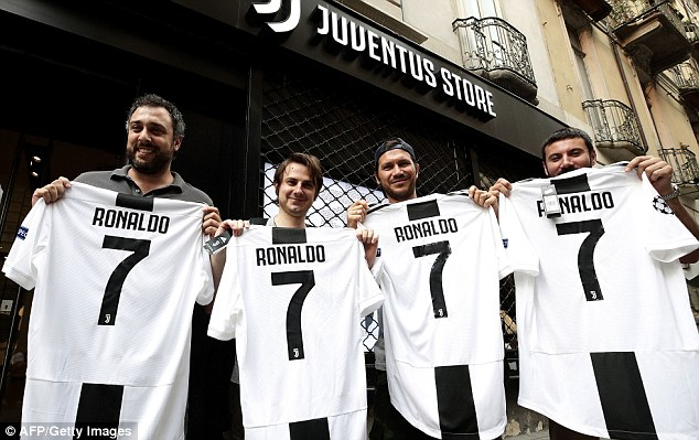 Fans pose with Ronaldo No 7 shirts after he agreed to join Juve in a £100m deal on Tuesday
