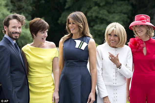 Amelie Derbaudrenghien, the partner of Belgian Prime Minister Charles Michel, second left, speaks with first lady Melania Trump, center, and French first lady Brigitte Macron, second right, during a group photo