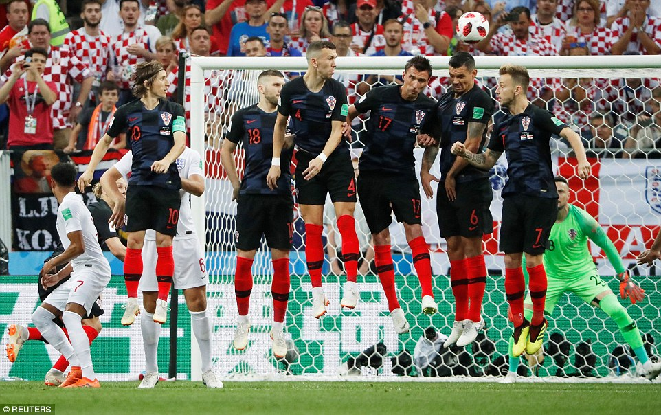 Perisic, Mandzukic and Dejan Lovren leap high but cannot block the free-kick as it bends towards their goal in the early stages