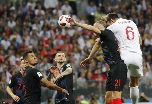 Harry Maguire leaps ahead ofCroatia centre-back Domagoj Vida but cannot direct his header from a corner goalwards