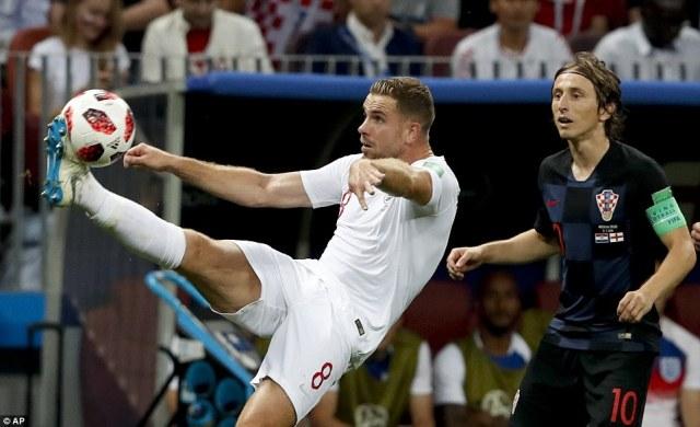 England midfielder Jordan Henderson gets his foot on the ball as Croatia captain Luka Modric watches in earnest