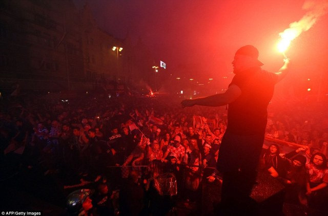 A man stands before a crowd in Zagreb while holding a flare after watching Croatia defeat England in Moscow
