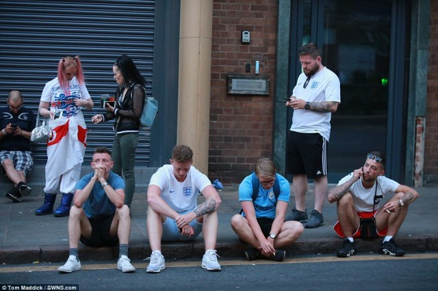Fans' anguish: Men sat in silence along the roadside in Nottingham just hours after jubilant scenes in the English city