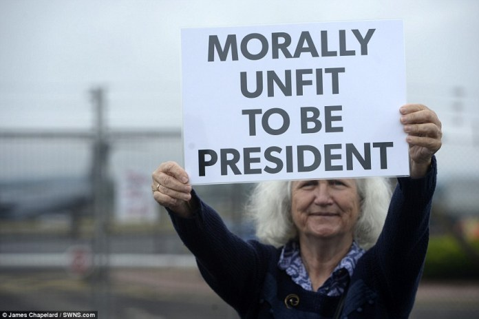 Nearby, a protest was held, including by a woman holding a card reading: 'Morally unfit to be president'