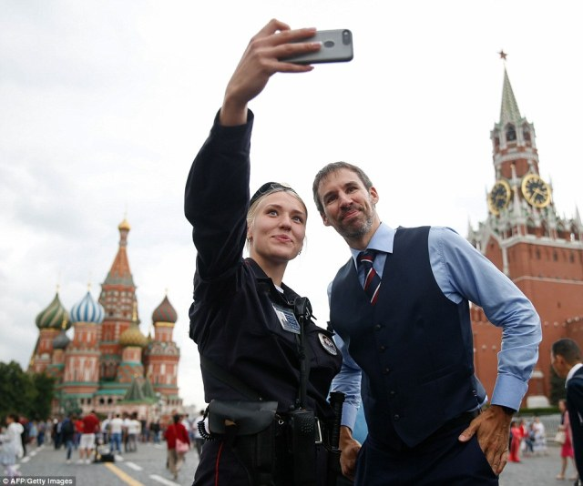 A Russian police officer poses with a Gareth Southgate lookalike in Moscow's Red Square