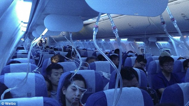 Oxygen masks can be seen hanging down into the cabin on an Air China flight that dropped 25,000 feet. There are claims the pilots had been smoking in the cockpit
