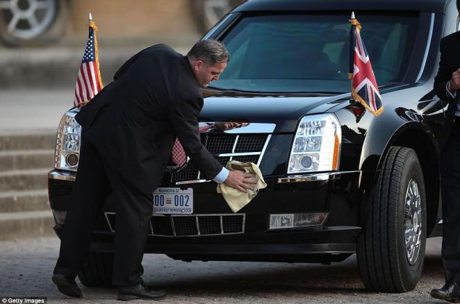 A member of security cleans the limousine of U.S. President Donald Trump and First Lady Melania Trump at Blenheim Palace last night