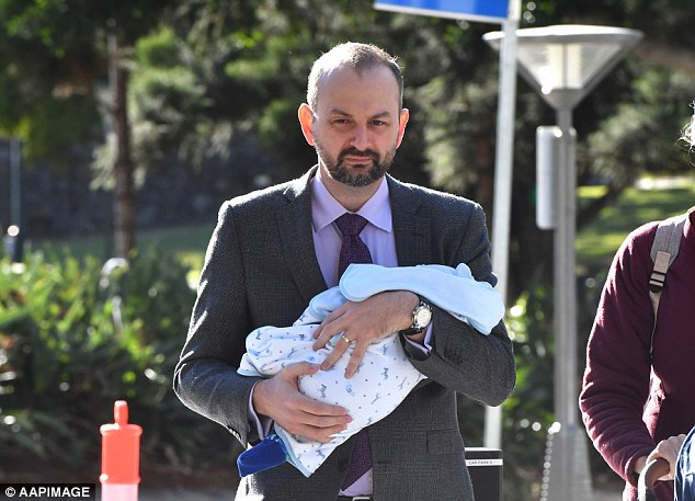 A former One Nation staffer on trial for rape has arrived in court cradling a newborn baby (pictured)