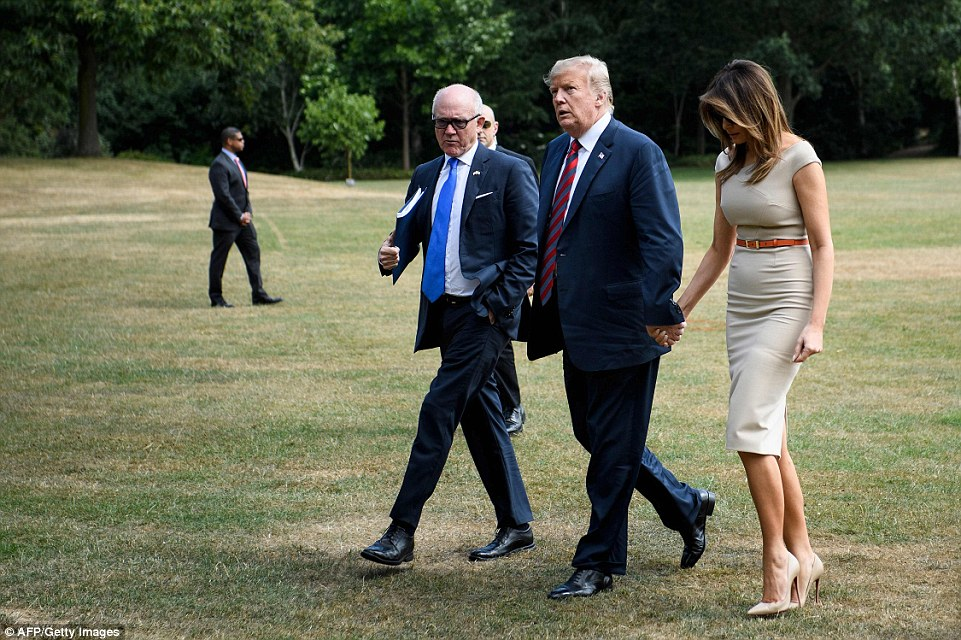 Mr Trump and Melania hold hands and talk to US Ambassador Woody Johnson, who will give them a place to stay tonight