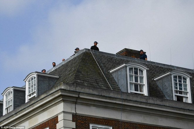 British police snipers watch from the roof of Winfield House as Donald Trump leaves after a night there with First Lady Melania