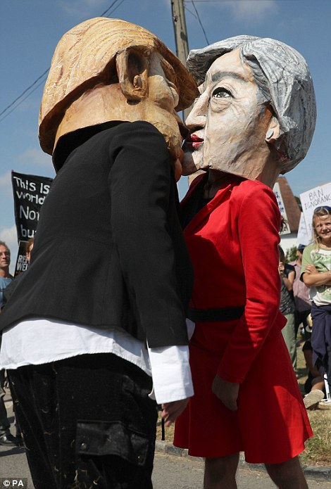 Protestors wearing Donald Trump and Theresa May paper mache heads join the protest and many believe the Queen should not be seeing him today