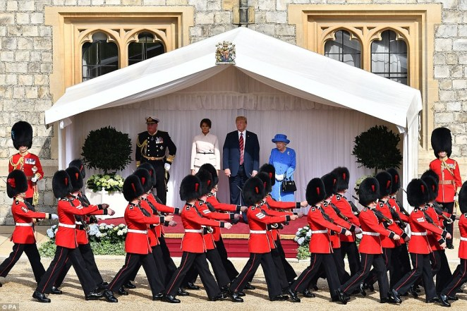 Off they go: The Queen's Guard marched in front of the trio as they looked on at the ceremonial procession