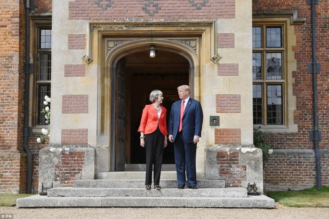 US President Donald Trump stands with Prime Minister Theresa May on the doorstep at Chequers, after he arrived for talks at her country residence in Buckinghamshire