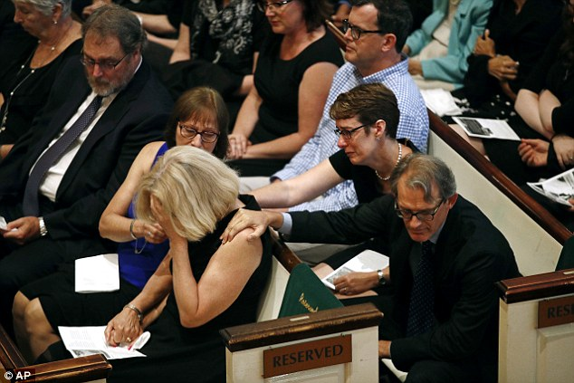 Chamblee drops her head into her hand at the funeral for her husband McNamara after he was one of the five journalists killed in the shooting at the Capital Gazette newspaper