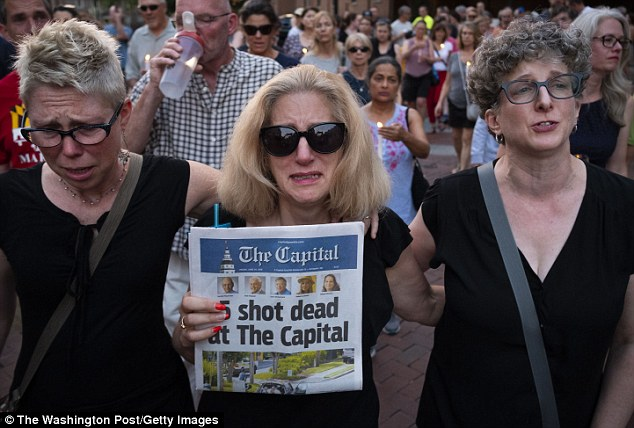 Chamblee, pictured center, marched at a vigil held the day after the shooting, clutching onto a headline by the paper announcing the death of her husband