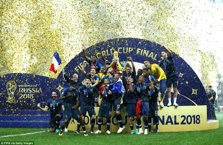 Hugo Lloris of France lifts the World Cup trophy to celebrate with his team-mates as the rain pours down in Moscow