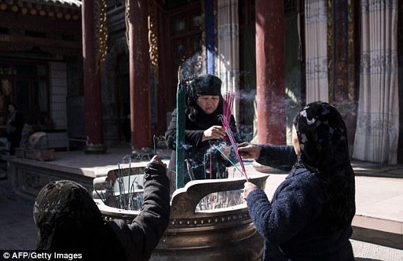 Hui Muslim women praying in a courtyard at a religious site in Linxia, Gansu province