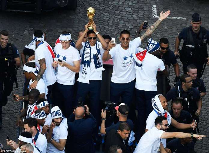 Defender Raphael Varane was seen holding up the World Cup trophy as he was surrounded by his teammates. Pictured, left to right: midfielder Corentin Tolisso, defender Benjamin Pavard, Mr Varane, goalkeeper Alphonse Areola and midfielder Blaise Matuidi