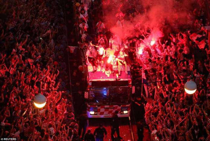 The players were seen sat on top of the bus holding flares as crowds attempted to catch a glimpse of them