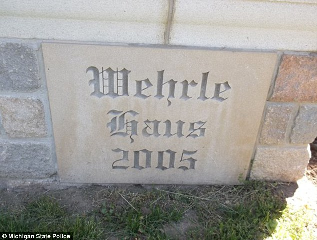 The words 'Wehrle Haus 2005' are etched into a stone at the base of the priest's home