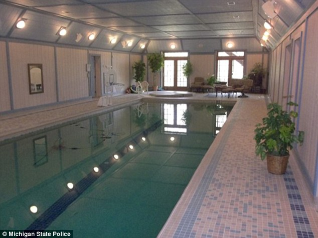 A large swimming pool and hot tub are located inside the stately residence