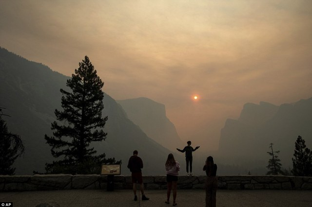 Hannah Whyatt poses for a picture as smoke from the Ferguson wildfire obscures the sun in Yosemite Valley