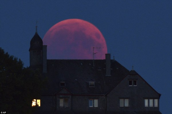 The moon turns red during the lunar eclipse in Bernkastel-Kues, Germany this evening as Mars appears brighter than usual