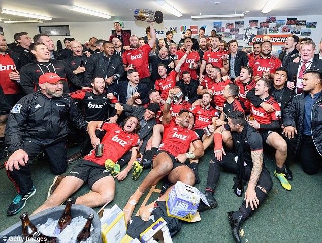 Joe Moody of the Crusaders lifts the Super Rugby Trophy in their dressing room after their win