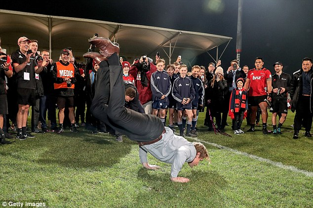 Crusaders head coach Scott Robertson celebrates their victory with a breakdance on the pitch