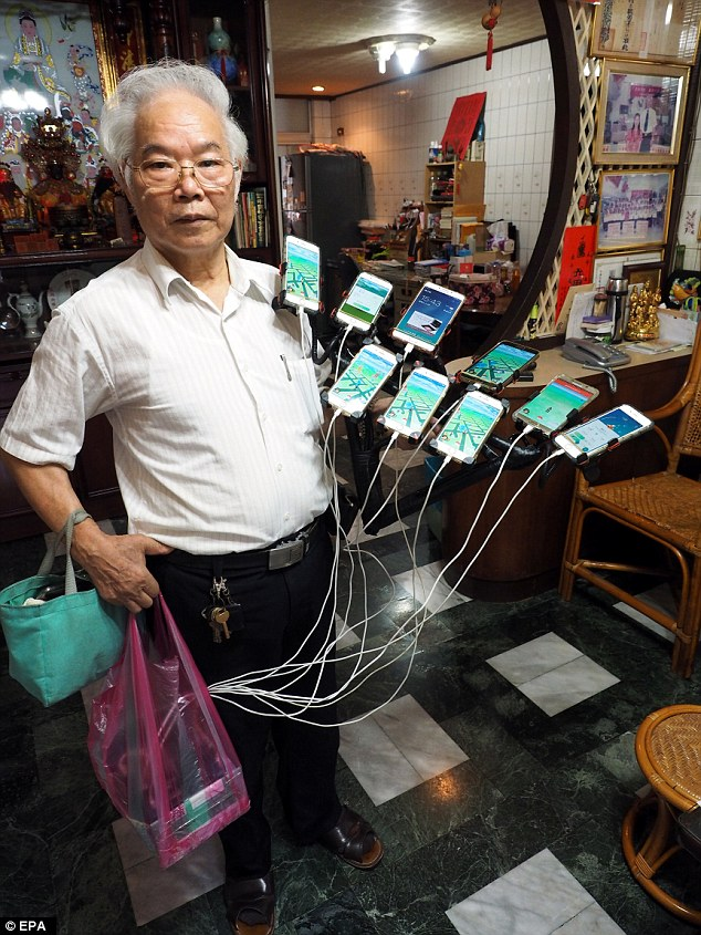 Chen San-yuan rigged up 11 smartphones on his bicycle (pictured is him holding the handlebar with them attached) to catch hundreds of digital monsters a day playing Pokemon Go