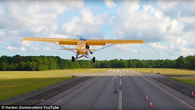 Bullard leaned out the doorless plane and dropped a shot at a hoop set up on a landing strip as the plane flew over it at about 70 mph