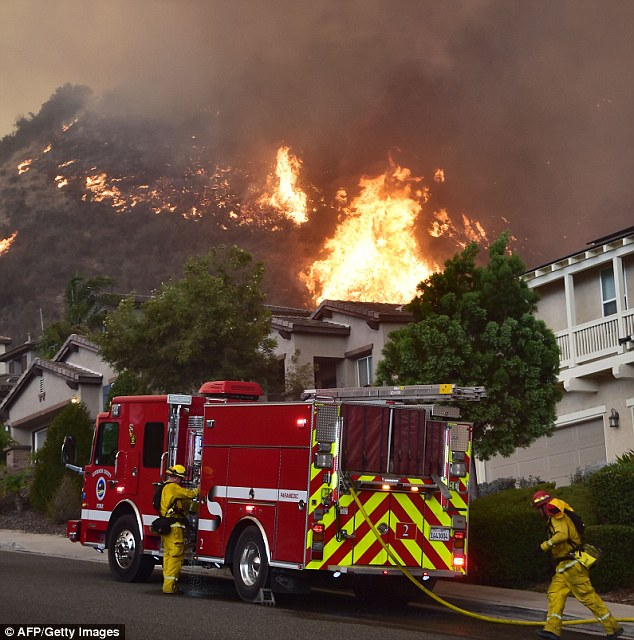 Firefighters are battling to protect homes at the Holy Fire in Lake Elsinore, California