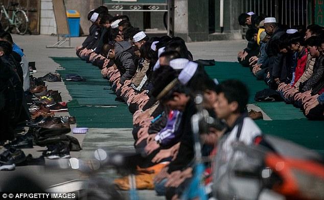 Ethnic Hui Muslim men praying at Nanguan Mosque during Friday prayers in Linxia, Gansu