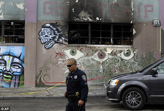An Oakland police officer guards the area in front of the art collective warehouse known as the Ghost Ship in the aftermath of a fire