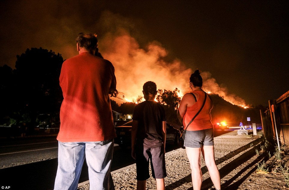 Residents watch the Holy Fire burning in the Cleveland National Forest in Lake Elsinore, California on Thursday