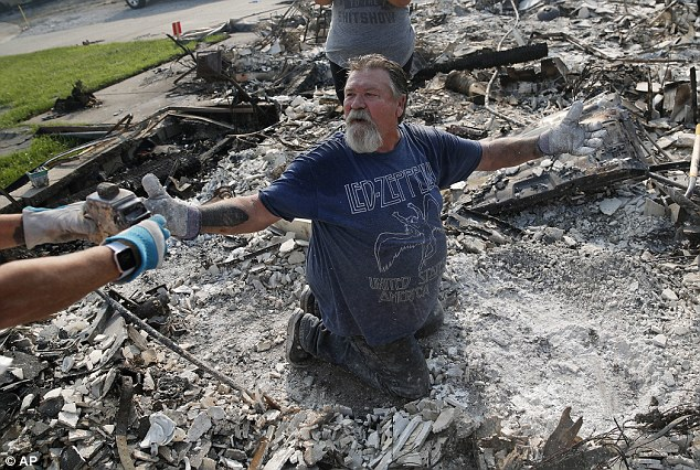 Rick Kincaid reacts as he finds his childhood toy as they sift through the charred remains of their home burned in the Carr Fire, Saturday, Aug. 11, 2018in Redding, Calif