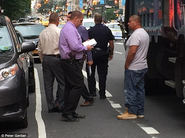 Garbage truck driver, Felipe Chairez, 44, (right) appeared to be drunk when police arrived at the scene. He is pictured being questioned by police