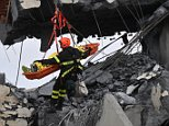 Rescuers at work to recover an injured person after a highway bridge collapsed in Genoa, Italy