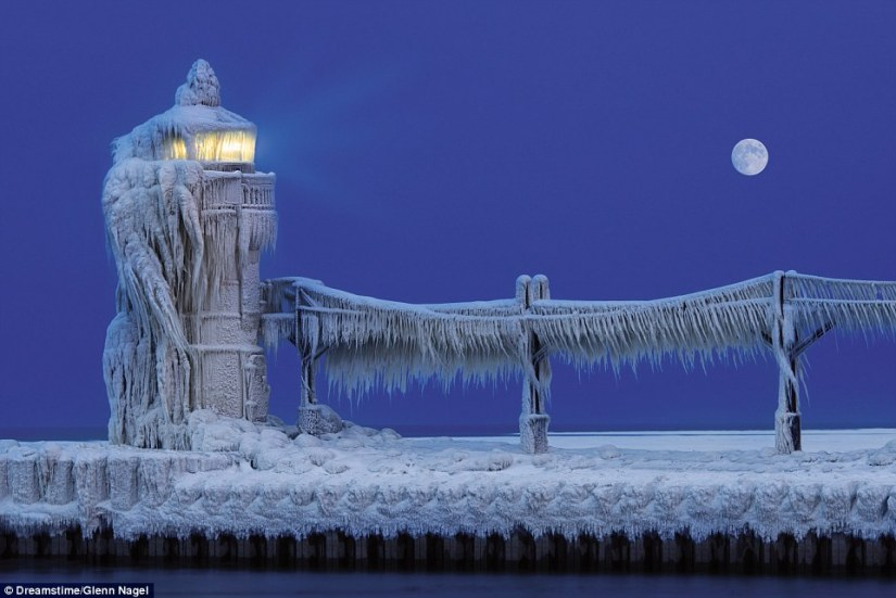 Thick ice clings to the Outer Lightouse at St Joseph North Pier on Lake Michigan in the USA. It has a 35ft iron tower and raised access walkway, at the end of the harbour breakwater. Since 2008, the outer and inner lights have been managed by the city as a historic site
