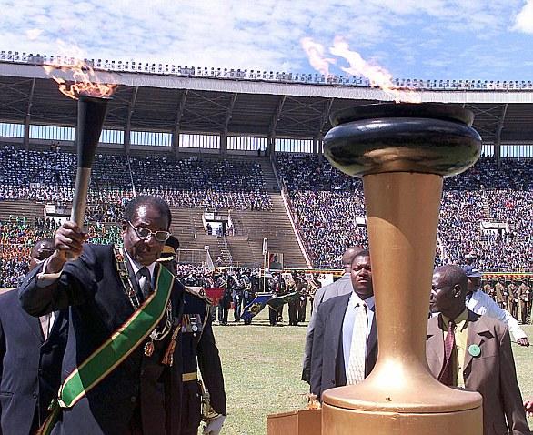 Former Zimbabwean President Robert Mugabe lights independence lighthouse at crowded stadium