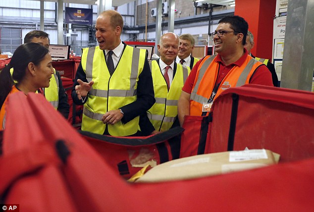 Prince William smiles as he talks to Royal Mail sorting office workers during a visit to the Royal Mail international distribution centre near Heathrow airport in Slough