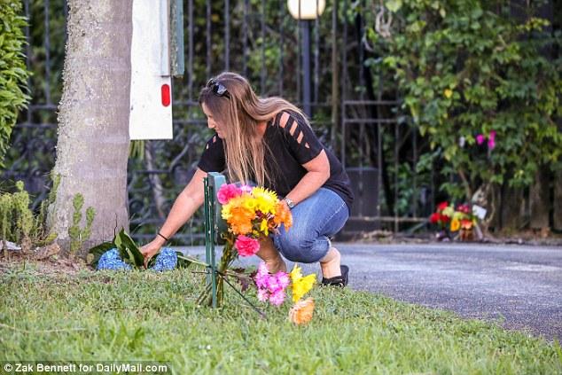 Une femme place des fleurs devant la maison de Burt Reynolds en Floride peu après sa mort jeudi